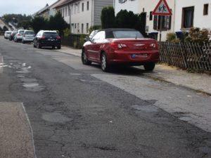 Ein Foto (Mathilde Thiel), das den schlechten Zustand der Straße zeigt.